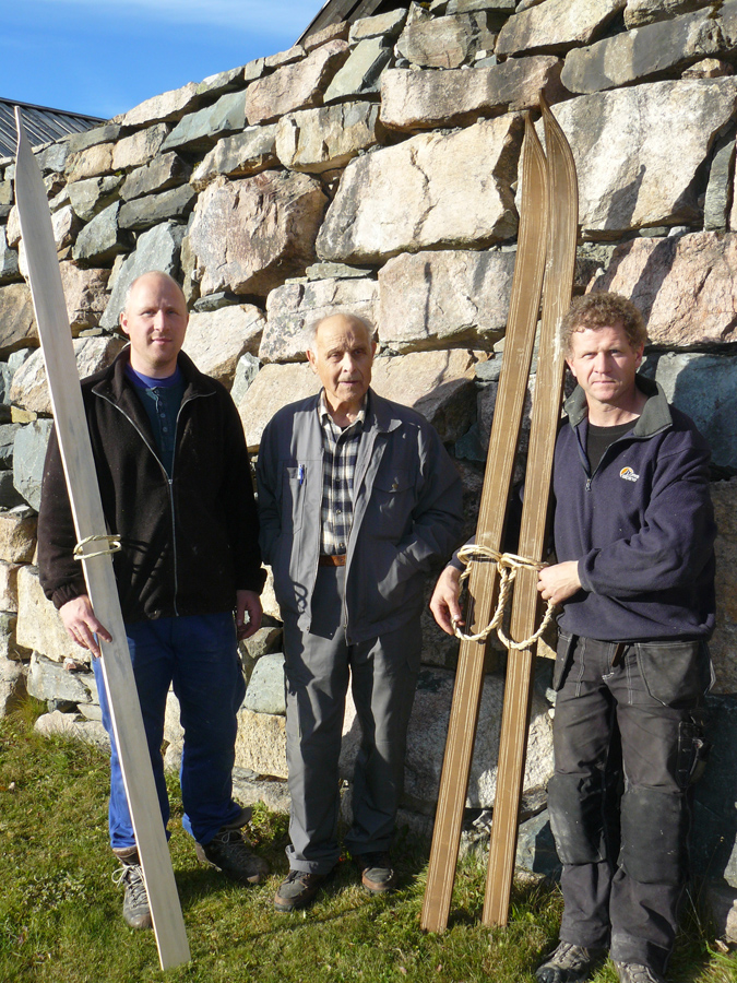 Terje Haugen, Åsmund Kleiv and Tarjei Gjelstad posing with a pair of traditional skis